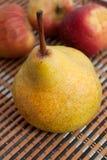 Poire jaune avec les pommes rouges Photos stock