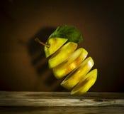 Poire mûre coupée en tranches fraîche avec des feuilles accrochant dans le ciel Photographie stock