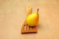 Poire sur une spatule en bois Photo libre de droits