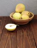 Poires dans un plat sur la vieille table en bois Photographie stock libre de droits