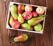Poires et pommes dans la boîte en bois sur la table Image stock