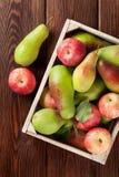 Poires et pommes dans la boîte en bois sur la table Photographie stock libre de droits