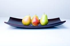 Poires fraîches délicieuses dans un vase en bois sur une table Images libres de droits