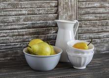 Poires fraîches en cuvette et vaisselle de vintage sur un fond en bois foncé Images stock