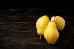 Poires fraîches mûres jaunes sur le vieux conseil en bois image libre de droits