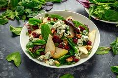 Poires fraîches, salade de fromage bleu avec le mélange vert végétal, noix, canneberge Nourriture saine Photos stock