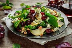 Poires fraîches, salade de fromage bleu avec le mélange vert végétal, noix, raisins rouges Nourriture saine Photos libres de droits