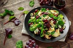 Poires fraîches, salade de fromage bleu avec le mélange vert végétal, noix, raisins rouges Nourriture saine Image libre de droits