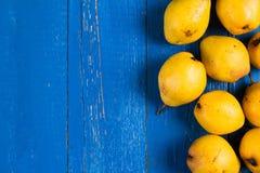 Poires organiques mûres fraîches de yello sur la table en bois rustique bleue, fond naturel, nourriture de régime Images libres de droits