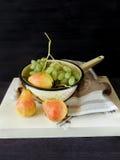 Poires sur un conseil en bois et des raisins verts dans une passoire Photos libres de droits