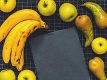 Poires vertes de conférence, pommes vertes, bananes, une planche à découper s Images stock