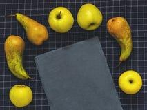 Poires vertes de conférence, pommes vertes, une ardoise de planche à découper sur b Image stock