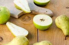 Poires vertes douces fraîches avec des pommes sur la table en bois Image stock