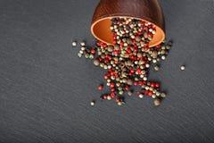 Pois colorés multi dispersés de poivre dans un plat d'argile dans le cente Photographie stock libre de droits