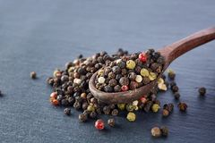 Pois de poivre noir dans une cuillère sur un fond en pierre Photographie stock