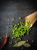 Pois en papier et poivrons de piment sur un fond en bois foncé Photo stock