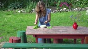 Pois sains de vert de coquille de cosse de fille de jeune fille sur la table en bois 4K clips vidéos
