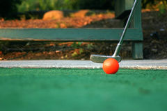Poised To Putt. A miniature golf ball and putter Royalty Free Stock Photography