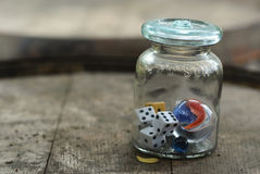 Poison. Dice and marbles in vintage glass poison jar on rustic whiskey barrel Stock Photo