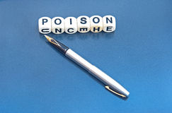 Poison pen letter. Text 'poison' in black upper case letters on small white cubes together with silver fountain pen  on gray background Royalty Free Stock Photos