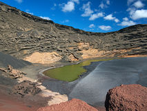 The poisonous green volcanic lake in the crater caldera. Black hardened lava and the erosion of the slopes Stock Image