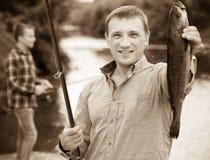 Poisson d'eau douce de crochet de participation de pêcheur dans des mains Image stock