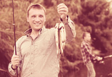 Poisson d'eau douce de crochet de participation de pêcheur sur la rivière Images libres de droits