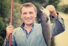 Poisson d'eau douce positif de crochet de participation de pêcheur Photographie stock