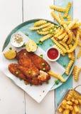Poisson-frites servis avec des sauces et des pois Photographie stock