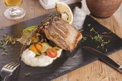 Poisson-frites traditionnels britanniques avec les pois écrasés, sauce à tartre sur la bière froide de papier chiffonnée image libre de droits