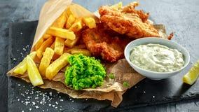 Poisson-frites traditionnels britanniques avec les pois écrasés, sauce à tartre sur le papier chiffonné Photographie stock