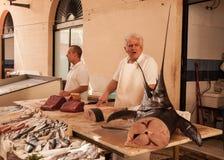 Poissonnier vendant des espadons sur un vieux marché local Photos libres de droits