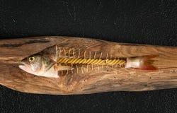 Poissons abstraits de pâtes sur le conseil en bois images stock