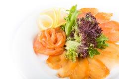 Poissons assortis d'un plat avec de la laitue et le citron sur un fond blanc Un plat des poissons assortis Photographie stock libre de droits