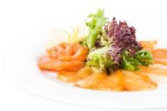 Poissons assortis d'un plat avec de la laitue et le citron sur un fond blanc Un plat des poissons assortis Fin vers le haut Images libres de droits