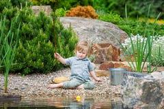 Poissons contagieux occupés de petit garçon dans l'étang Photos stock