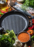 Poissons crus crus de bar avec des légumes, des grains, des herbes et des épices sur le hachoir, fer grillant la casserole au cen Photo stock
