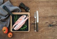 Poissons crus crus de mulet rouge dans une casserole à cuire avec le romarin, le citron et l'ail au-dessus du fond en bois rustiq Photos stock