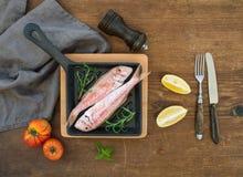 Poissons crus crus de mulet rouge dans une casserole à cuire avec le romarin, le citron et l'ail au-dessus du fond en bois rustiq Photographie stock