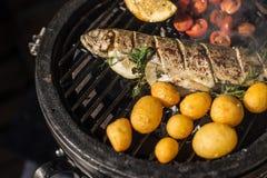 Poissons délicieux de truite arc-en-ciel avec des tomates, des pommes de terre et le citron faisant cuire sur le gril flamboyant  Photo libre de droits