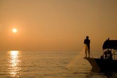 Poissons de crochet avec le filet au lever de soleil images stock
