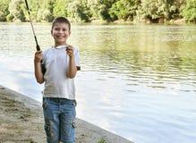 Poissons de crochet de garçon sur l'amorce, le camping d'enfant et la pêche, la rivière et la forêt, saison d'été Image stock