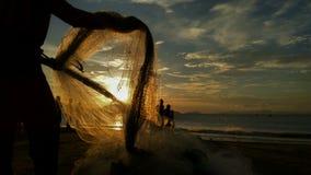 Poissons de crochet de pêcheurs quand coucher du soleil Images libres de droits