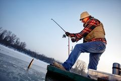 Poissons de crochet de pêcheur sur la rivière congelée en hiver Photos libres de droits