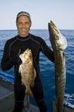 Poissons de la prise deux de pêcheur grands vers le haut Images stock