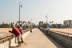 Poissons de personnes sur le pilier de pêche de plage de Venise en Californie du sud Image libre de droits