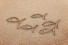 Poissons dessinés sur un sable de plage Photographie stock libre de droits