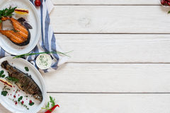 Poissons grillés sur l'espace libre en bois blanc de table Photographie stock libre de droits