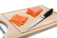Poissons saumonés crus frais sur le panneau en bois d'isolement Photos stock