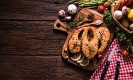 Poissons saumonés grillés avec l'assaisonnement et divers légumes photos stock